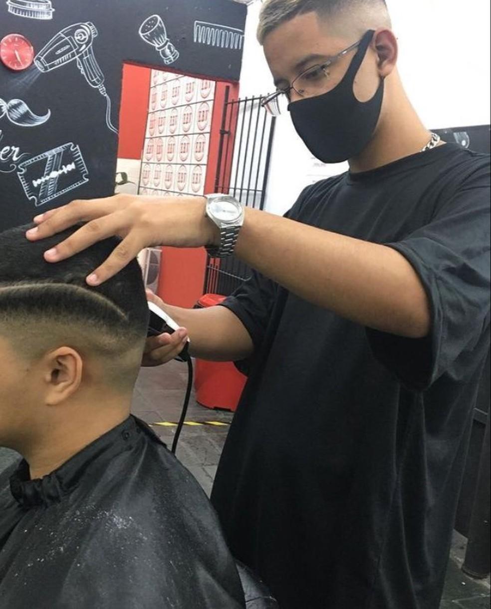 Jovem trabalha em barbearia de terça a sábado e se dedica a ato solidário aos domingos e segunda. Na foto, ele está em seu trabalho  — Foto: Arquivo pessoal