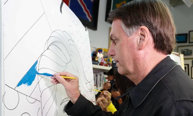 Em Miami, o presidente Jair Bolsonaro ajuda a pintar um quadro de Romero Britto