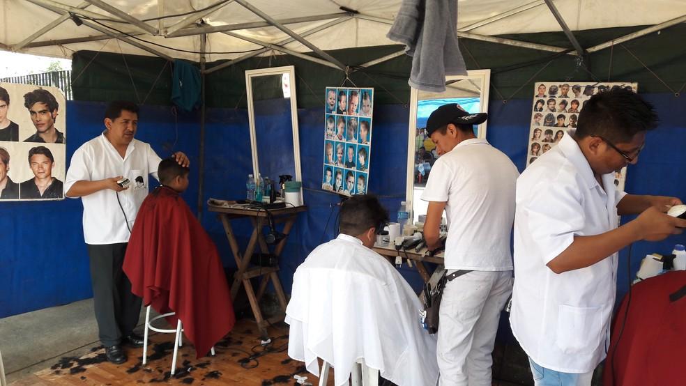 Bolivianos cortam cabelo na Praça Kantuta — Foto: Alexandre Alliatti