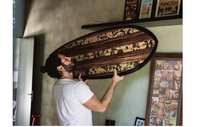 Parede de cimento queimado ganha charme extra com objetos de decoração, como pranchas de surfe e quadros (Foto: Reprodução)