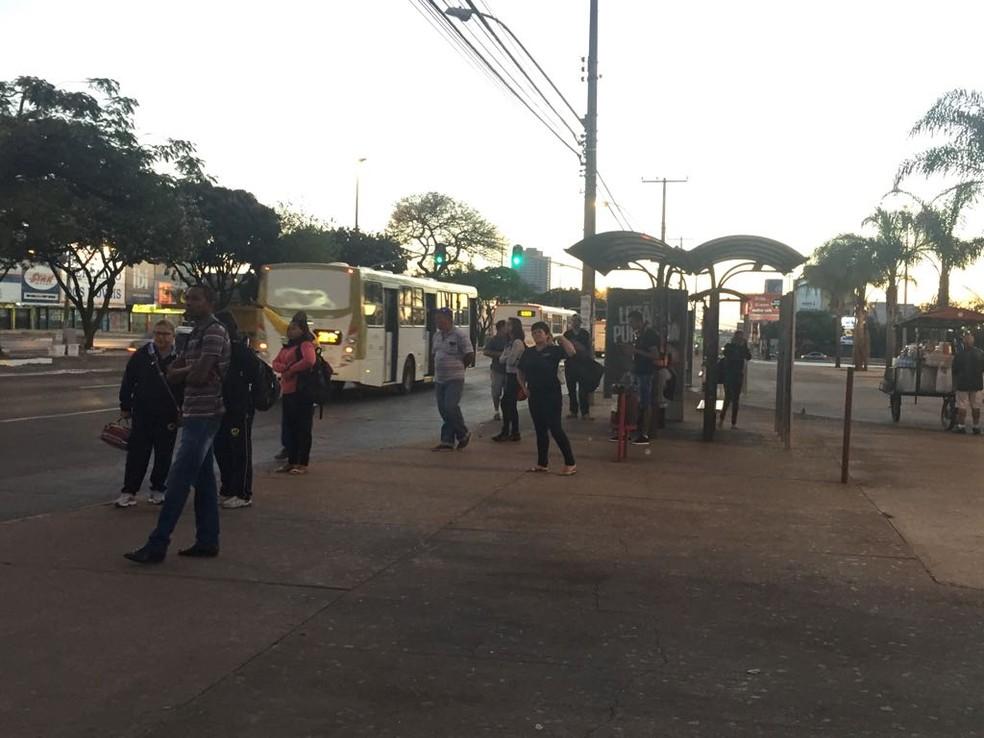 Passageiros aguardam ônibus na parada em frente à Feira Permanente de Ceilândia (Foto: Maria Fernanda Soares/TV Globo)