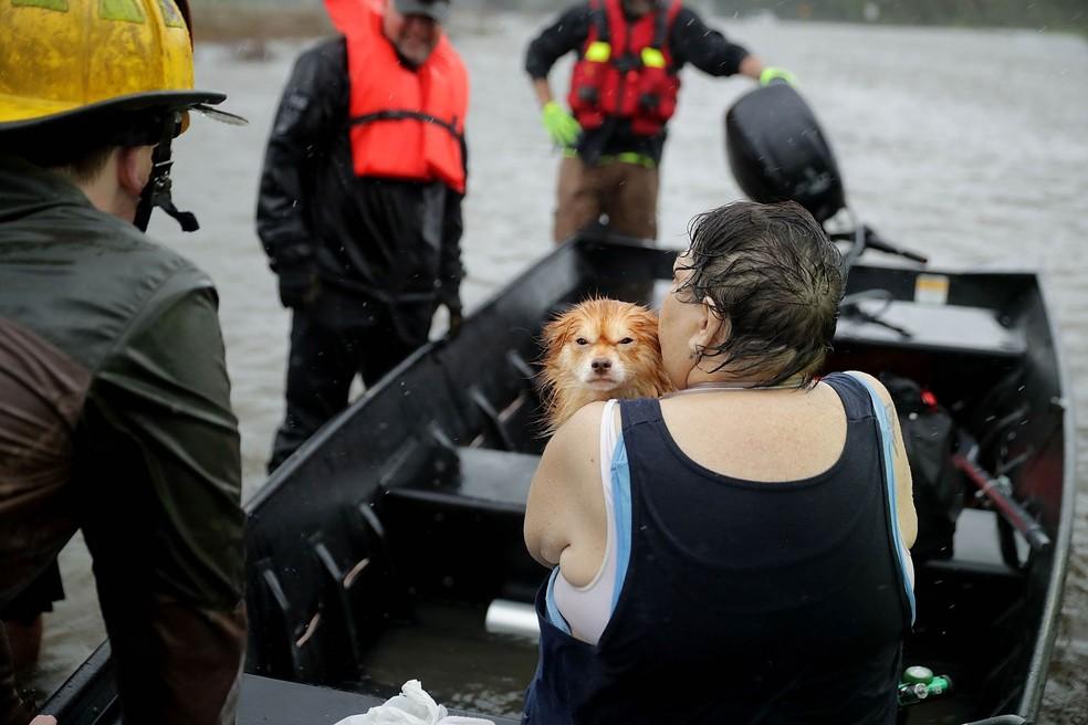 Mulher leva seu cachorro no colo ao ser resgatada em um barco por bombeiros e voluntários em James City, na Carolina do Norte, devido à chegada do furacão Florence — Foto: Chip Somodevilla/Getty Images via AFP