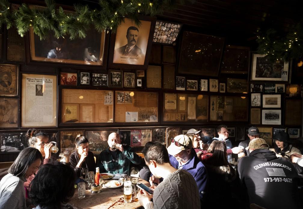 Clientes se sentam abaixo de fotos e documentos antigos, incluindo um pôster do vice-presidente Theodore Roosevelt, no McSorley's Old Ale House, em Nova York, em 27 de dezembro de 2019 — Foto: AP Photo/Mark Lennihan