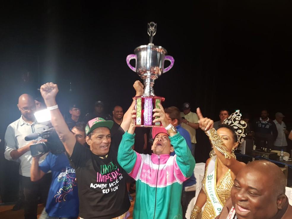 Luiz Alberto Martins, o Pelé, presidente da União Imperial, ergue o troféu após a vitória do carnaval santista (Foto: Mariane Rossi/G1)
