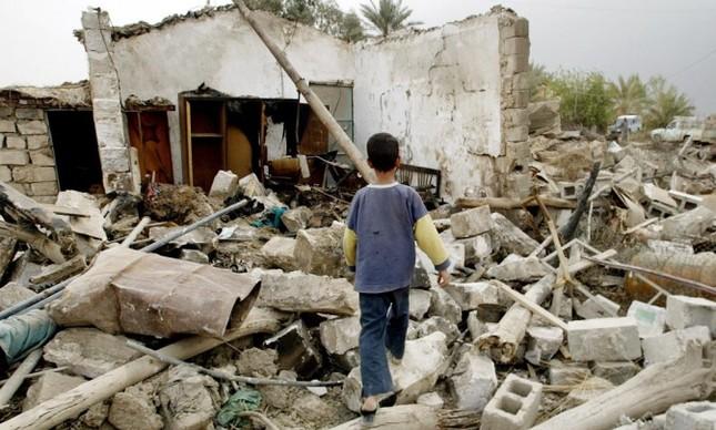 Um menino iraquiano diante dos destroços da casa da família na vila de al-Madaan, ao Sul de Bagdá