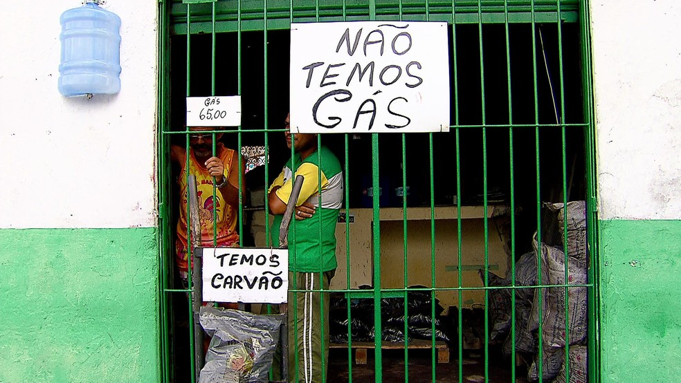 Comerciantes colam placas em revendedoras do Recife, informando que não há gás de cozinha, mas há sacos de carvão à venda (Foto: Reprodução/TV Globo)