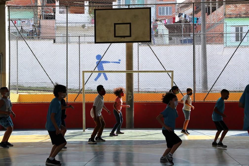 Crianças fazem exercícios na quadra poliesportiva da escola Thomaz Rodrigues Alckmin, no primeiro dia de retorno das escolas do estado de São Paulo para atividades extracurriculares — Foto: Amanda Perobelli/Reuters