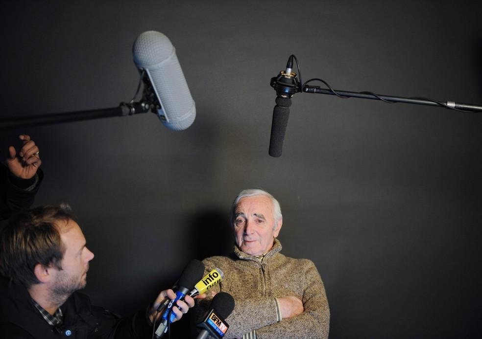 Nesta foto de arquivo tirada em 15 de janeiro de 2010, o cantor e compositor francês Charles Aznavour fala aos jornalistas após gravar, com uma dezena de rappers e pop stars franceses, um videoclipe para arrecadar fundos para o Haiti, atingido pelo terremoto em Paris. — Foto: Bertrand LANGLOIS / AFP