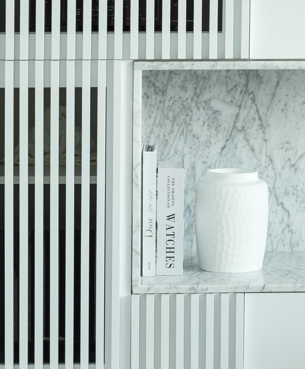 O armário ripado da sala dá acesso aos equipamentos eletrônicos do home cinema e ao ar-condicionado (Foto: Mariana Boro/Divulgação)