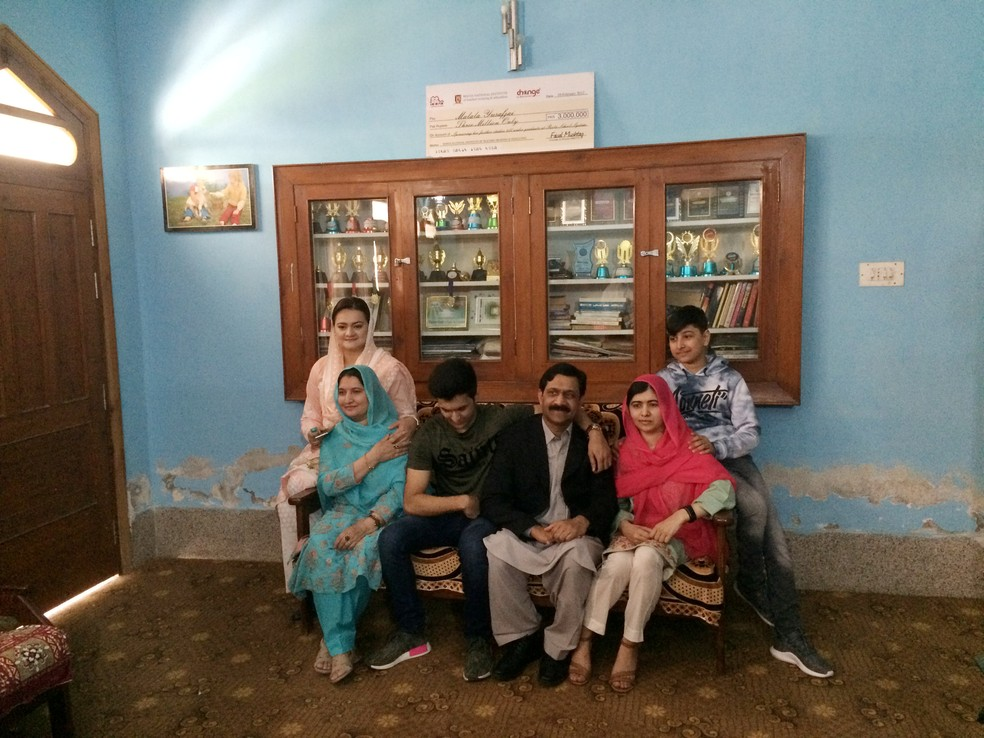 Malala Yousafzai posa com sua família em um dos cômodos de sua antiga casa durante visita a sua cidade natal Mingora, no Vale do Swat, no Paquistão, em março  — Foto: Stringer/Reuters