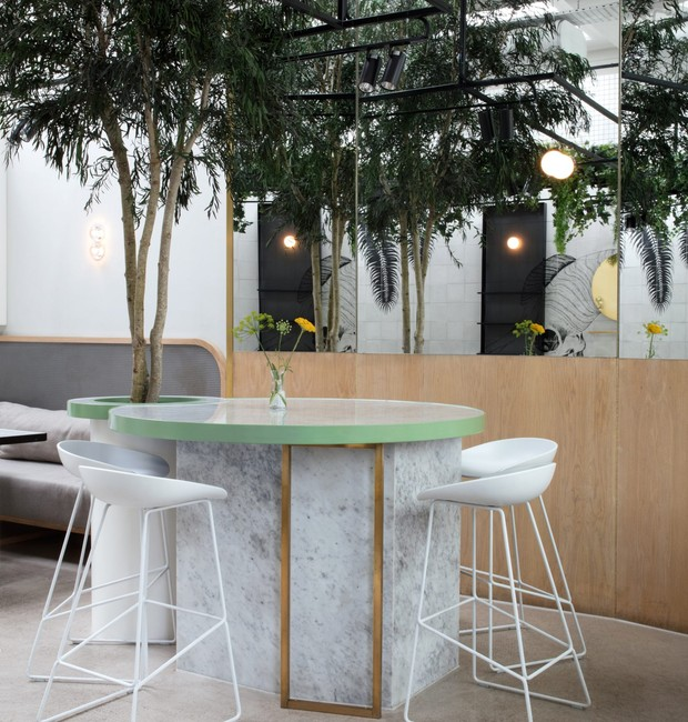 Os espelhos ampliam o local e favorecem o verde espalhado pelo café (Foto: Dezeen/ Reprodução)