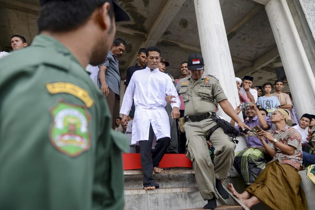 Jono Simbolon, cristão condenado pela venda de álcool, é conduzido a local em que recebeu chibatadas nesta sexta-feira (19) (Foto: Chaideer Mahyuddin/AFP)