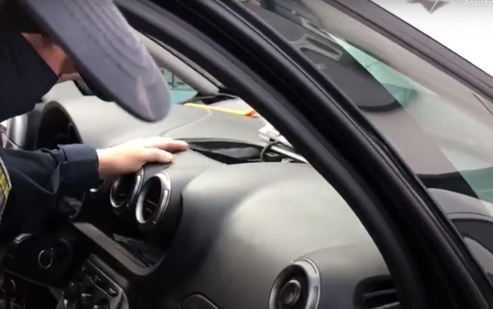Policiais retirando as armas que estavam escondidas no painel do carro, na Bahia — Foto: Divulgação/PRF