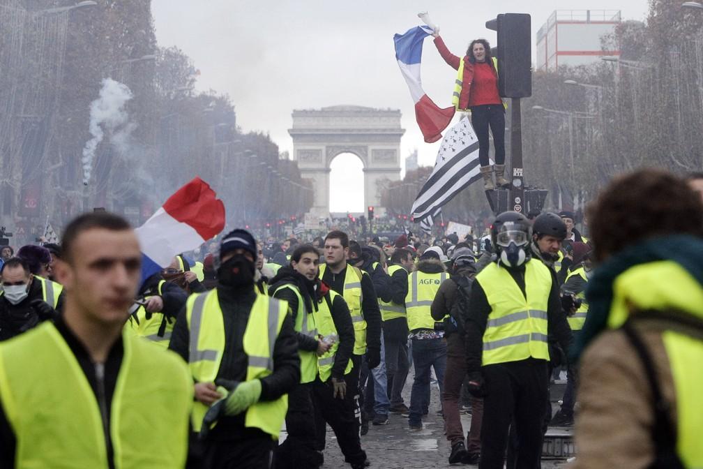 Imagem de 19 de novembro mostra manifestantes 'coletes amarelos' protestando na avenida Champs-Elysees, em Paris — Foto: Kamil Zihnioglu/AP Photo