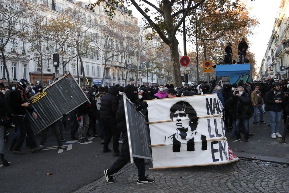 Imagem de Maradona é vista durante manifestações na França, onde milhares de pessoas protestam contra um projeto de lei sobre segurança — Foto: AP Photo/Francois Mori