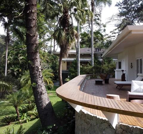 Após reforma, casa ganha deck curvo que conecta interiores ao jardim