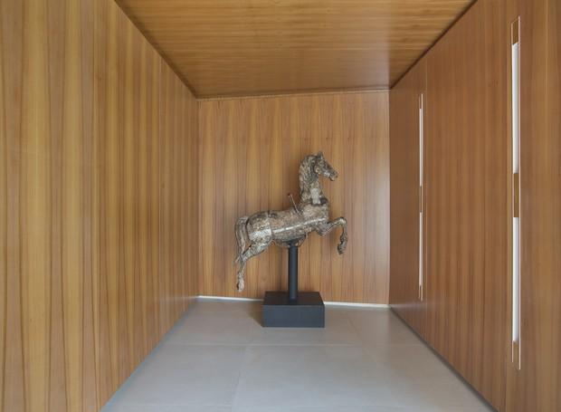O cavalo de carrossel é uma peça de antiquário que acompanha a família. Ganhou destaque ao ocupar o hall revestido de madeira, que parece emoldurar o ítem (Foto: Denilson Machado/MCA Estúdio/Divulgação)