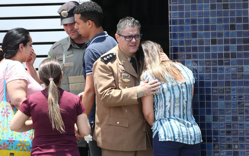 Mulher é consolada na frente do Colégio Goyases, em Goiânia, onde aluno abriu fogo contra colegas em sala de aula (Foto: Cristiano Borges/O Popular/Estadão Conteúdo)