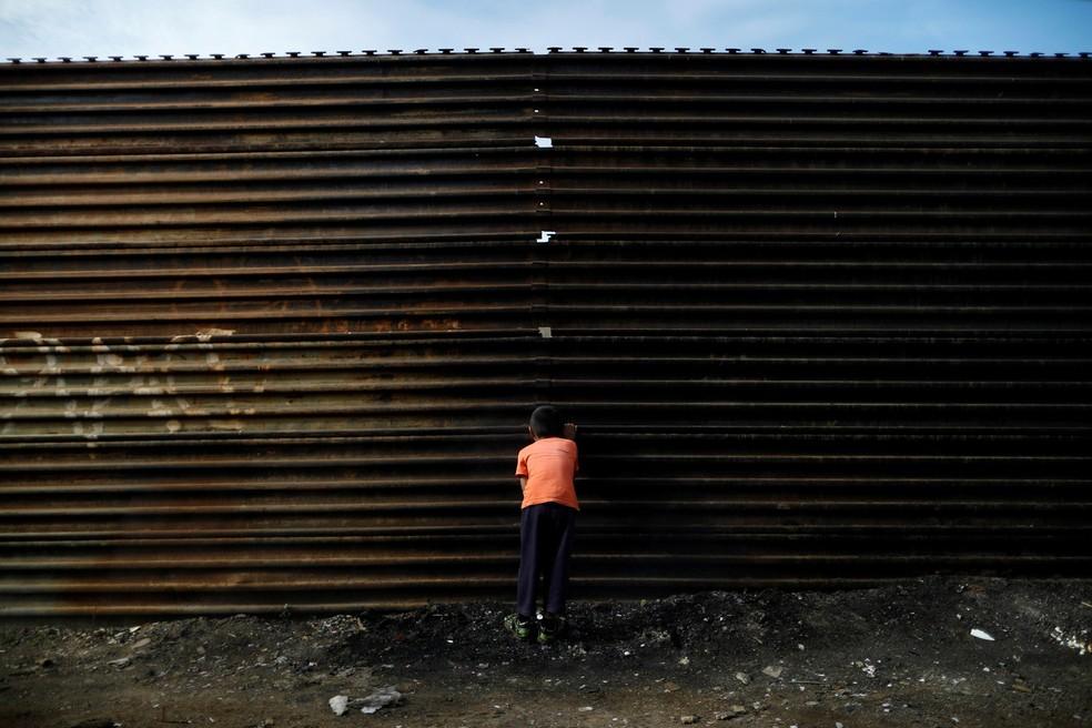 Um menino olha pelo buraco do atual muro na fronteira entre o México e os EUA em Tijuana, no lado mexicano (Foto: Edgard Garrido/Reuters)
