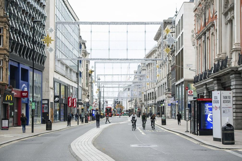 Ciclistas pedalam na Rua Oxford, em Londres, em meio a lojas fechadas pelo bloqueio total para conter a disseminação do novo coronavírus, no sábado (21). — Foto: Dominic Lipinski/PA via AP/Arquivo