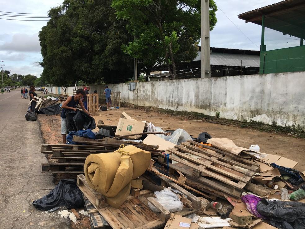 Venezuelanos recolhem restos deixados em acampamento esvaziado  — Foto: Emily Costa/G1 RR