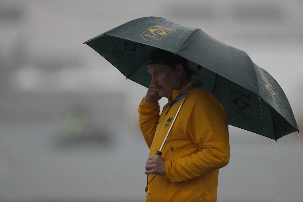 Técnico da Ana Marcela, Fernando Possenti, se proteje da chuva — Foto: Satiro Sodré/rededoesporte.gov.br