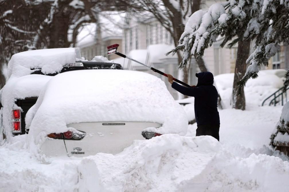 Homem tenta tirar grossa camada de neve em carro durante nevasca no nordeste dos EUA em 2 de fevereiro de 2021 — Foto: Elise Amendola/AP