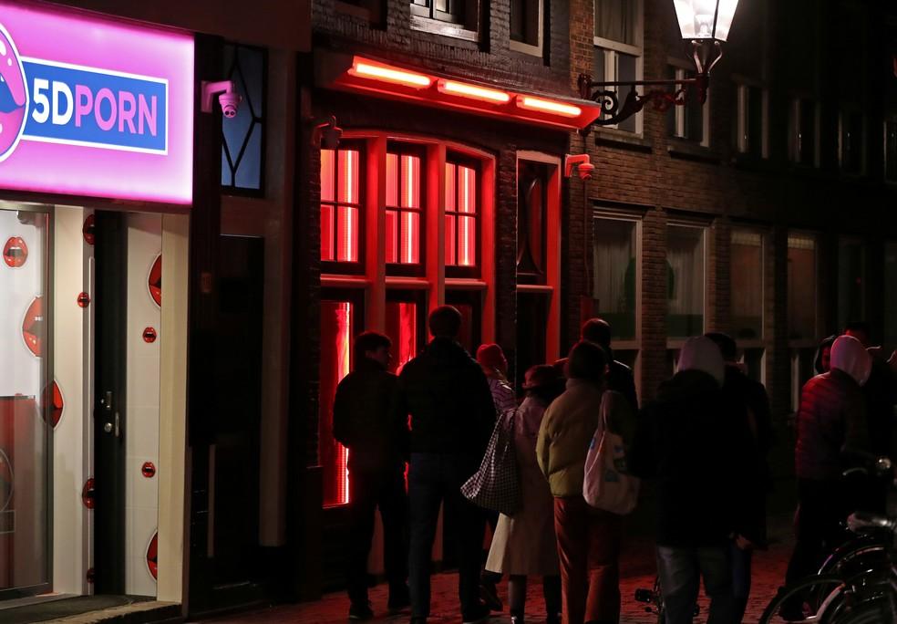 Pessoas passam pela porta de um bordel no Distrito da Luz Vermelha em Amsterdã, na Holanda. — Foto: Yves Herman / Reuters