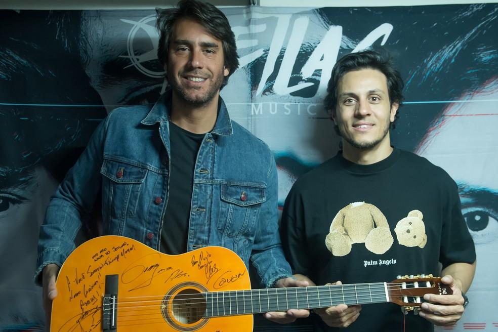 Paulo Velloso e Thiago Mansur, do Jetlag Music, posaram com o violão assinado pelas estrelas do VillaMix Uberaba — Foto: ANDRÉ SANTOS