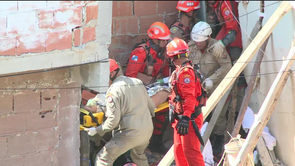Moradora é retirada de escombros de casa que desabou em Curicica — Foto: Reprodução / GloboNews