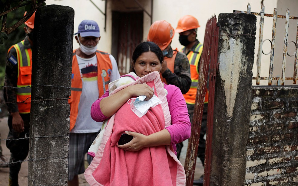 Mulher protege seu bebê enquanto soldados hondurenhos retiram moradores de área de risco por causa do furacão Iota, em Marcovia, na terça-feira (17) — Foto: Reuters/Jorge Cabrera