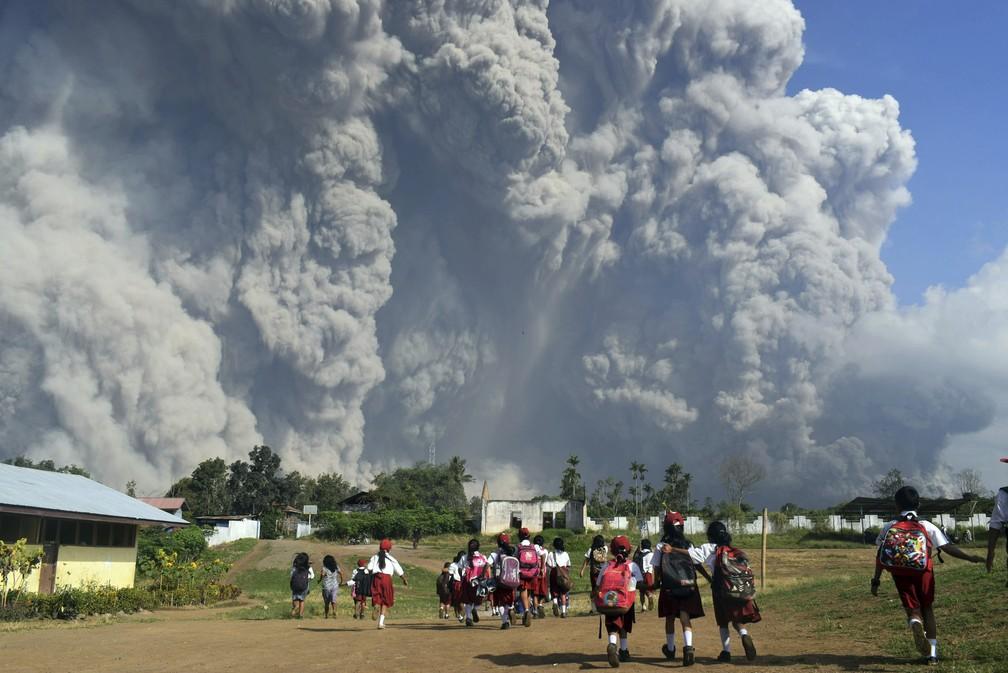 Crianças caminham em frente ao vulcão Mount Sinabung, que entrou em erupção na Sumatra do Norte, Indonésia  (Foto: Sarianto/AP)
