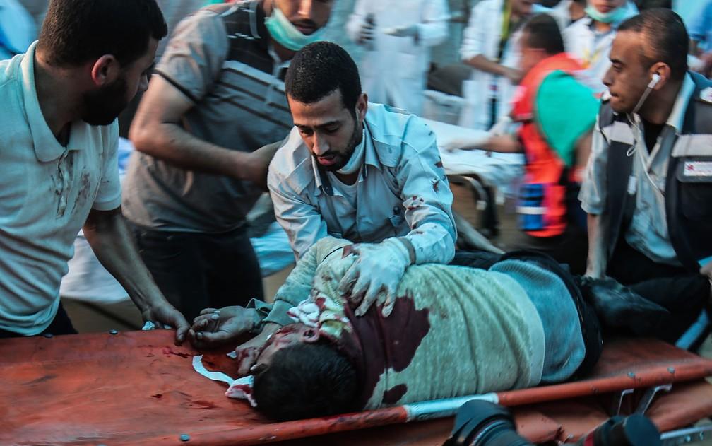 Médicos carregam Saadi Abu Taha, de 29 anos, ferido durante confrontos com forças israelenses em Khan Yunis, no sul da Faixa de Gaza, na sexta-feira (20). Segundo fotógrafo da AFP, Abu Taha morreu (Foto: Said Khatib/AFP)