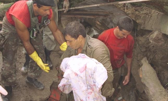 Bombeiro carrega corpo de bebê após deslizamento na Rocinha, em fevereiro de 1996