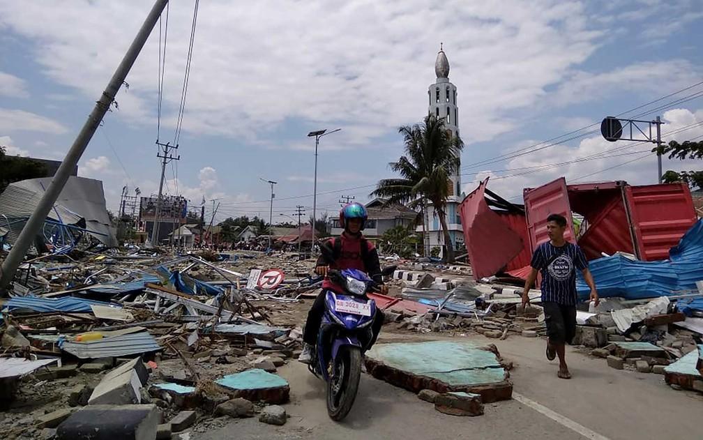 Pessoas tentam circular em rua cheia de escombros na ilha de Sulawesi — Foto: Muhammad Rifki / AFP