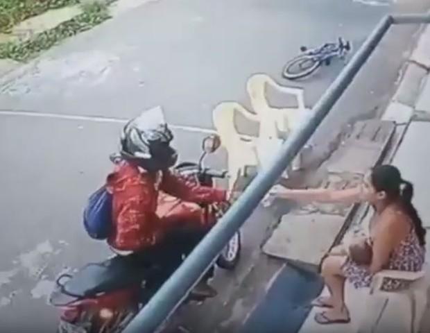 Mulher entrega o celular ao bandido (Foto: Reprodução)