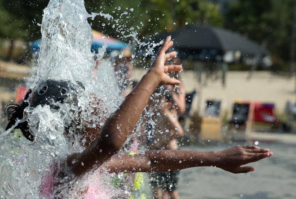 Uma menina se refresca pulando em uma fonte de água em Antwerp, na Bélgica. A temperatura no país chegou a 40,6ºC nesta quinta-feira (25), registrando um novo recorde de calor. A máxima anterior era de 36,6ºC, de junho de 1947 — Foto: Virginia Mayo/AP