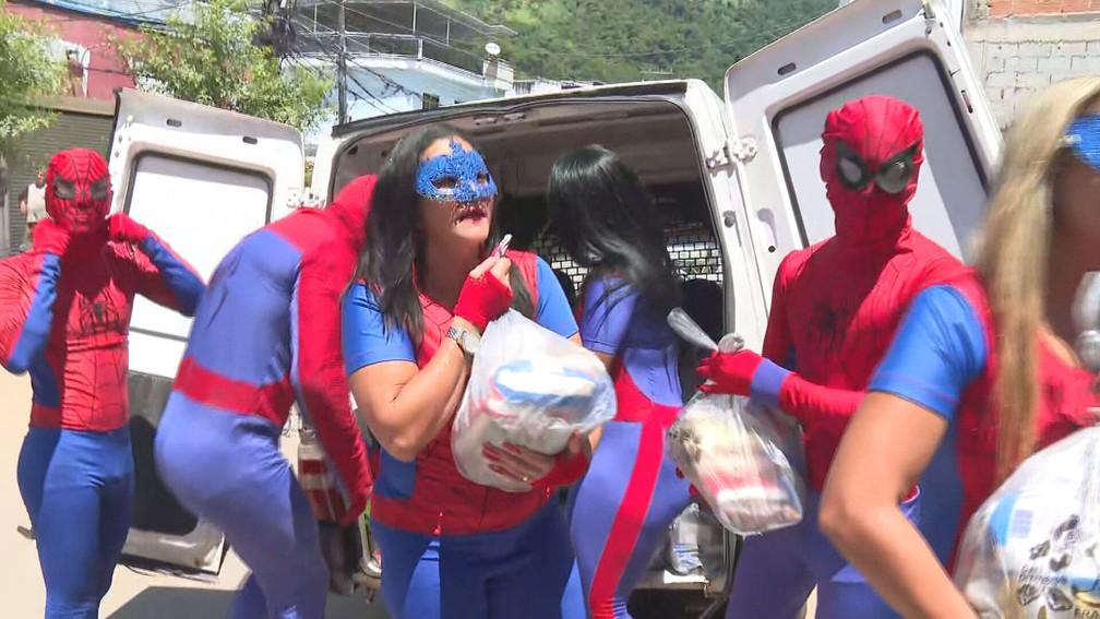 Voluntários se vestem de super-heróis e entregam donativos às vítimas das chuvas em Realengo — Foto: Reprodução/TV Globo