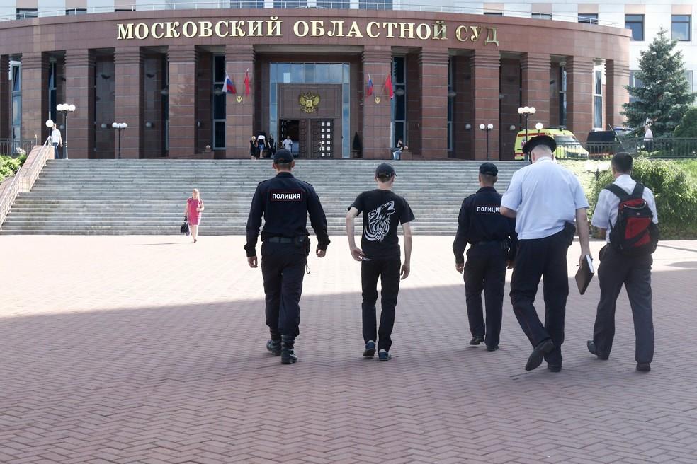 Policiais caminham em direção ao Tribunal Regional de Moscou, na Rússia, nesta terça-feira (1º) após réus tentarem roubar armas de segurança durante julgamento (Foto: Andrey Nikerichev/Moscow News Agency via AP)