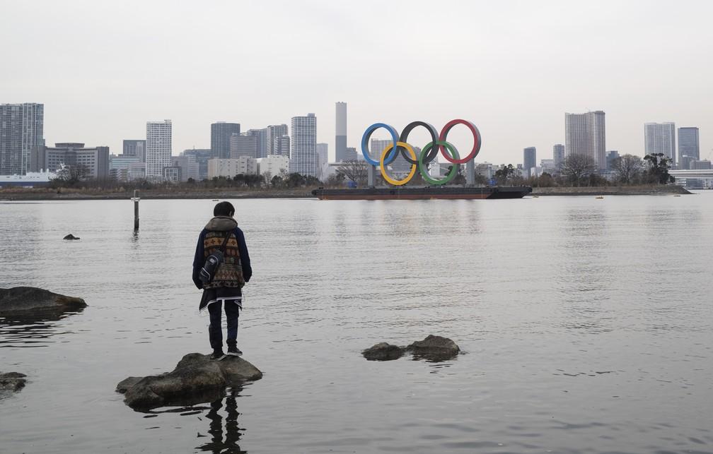 Um homem para em cima de pedra no parque marinho Odaiba, onde estão exibidos os aros olímpicos em Tóquio — Foto: Hiro Komae/AP