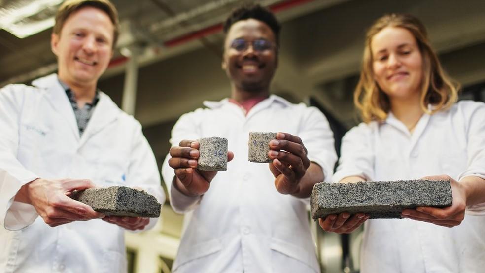 Dyllon Randall com os estudantes Vukheta Mukhari e Suzanne Lambert: tijolos têm inicialmente um odor de amônia, que desaparece apos 48 horas — Foto: Robyn Walker/UCT