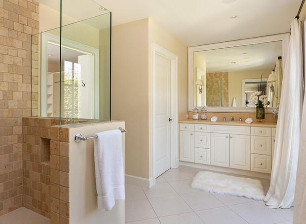A arquitetura dos banheiros não possui muitos detalhes, com azulejos claros e armários brancos,  (Foto: Berkshire Hathaway HomeServices/ Reprodução)