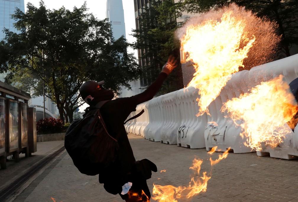 Manifestante pró-democracia lança um coquetel molotov durante uma manifestação perto do Complexo Central do Governo em Hong Kong, neste domingo (15)  — Foto: Tyrone Siu/ Reuters
