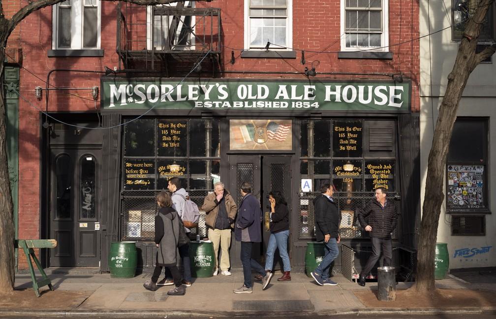 Pessoas entram e saem do McSorley's Old Ale House, em Nova York. O bar, aberto na metade do século 19, funcionou ilegalmente durante a Proibição, e continua em funcionamento — Foto: AP Photo/Mark Lennihan