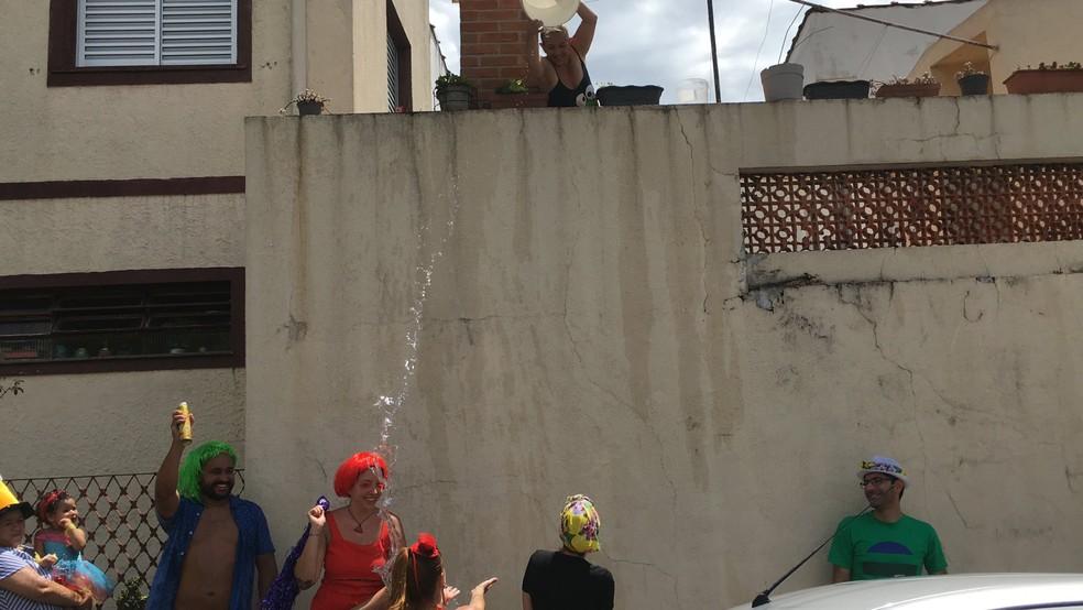 Com calor, muitos foliões ganharam um 'banho' dos moradores vizinhos do Saia de Chita. — Foto: Ana Carolina Moreno/G1