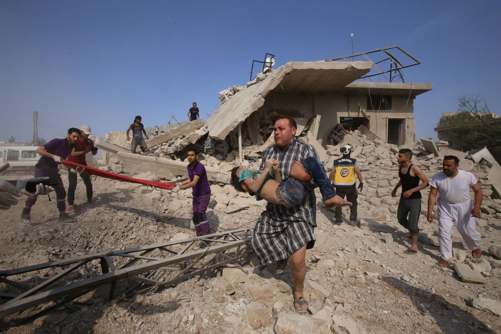 30 de maio - Um homem resgata uma criança enquanto membros da defesa civil síria, conhecidos como Capacetes Brancos, revistam a área em busca de sobreviventes após um ataque aéreo relatado por forças do regime e seus aliados em Maaret al-Noman, na província de Idlib, no sudoeste da Síria — Foto: Abdulaziz Ketaz/AFP