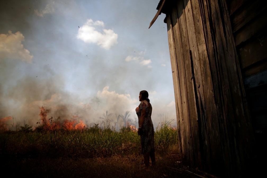 Incêndios na Amazônia: Moradora olha enquanto fogo se aproxima de sua casa perto de Porto Velho, no dia 16 de agosto. — Foto: Ueslei Marcelino/Reuters