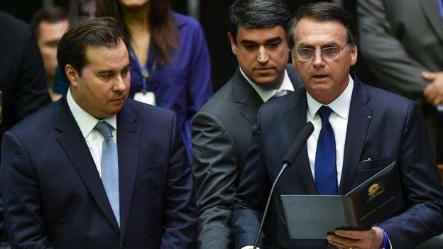 Bolsonaro faz o juramento de cumprimento à Constituição, ao lado de Rodrigo Maia; mais tarde, ele discursaria na rampa do Planalto  (Foto: AFP via BBC)