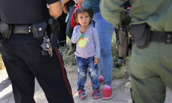 Menina migrante centro-americana observa policiais e agentes migratórios durante detenção de parentes, no Texas