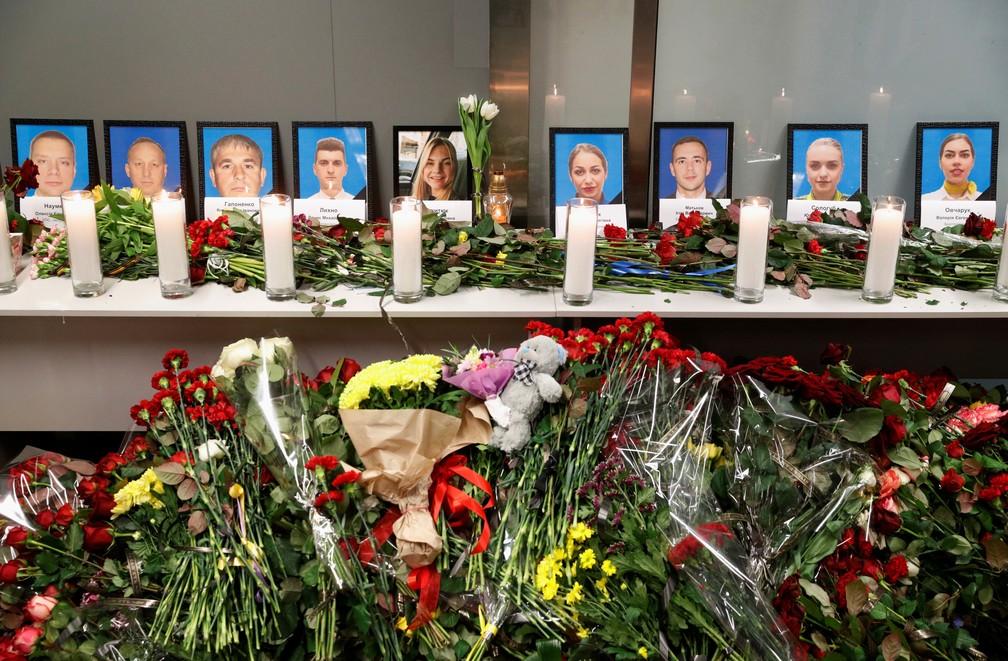 Flores e velas foram colocadas em frente às fotos da tripulação do avião ucraniano que caiu logo após decolar de Teerã, no Irã, nesta quarta (8). Nenhuma das 176 pessoas que estavam a bordo sobreviveu ao acidente. — Foto: Valentyn Ogirenko/Reuters
